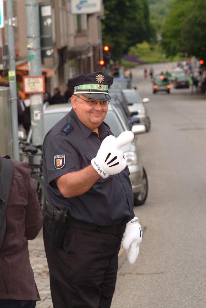 """Hier kommen wir in einen absoluten Grenzbereich. Dieser Polizist hat den Verkehr geregelt anlässlich des Besuchs hochrangiger Politiker auf der Kieler Woche.Eigentlich darffst Du das Foto ohne seine Genehmigung nicht veröffentlichen. Nun spielen hier besondere Aspekte eine Rolle. Der Polizist hat sich mit den Handschuhen """"verkleidet"""", durch die Uniform erweckt er in Kombination mit den Handschuhen Aufmerksamkeit. Es gibt neben diesem Foto weitere Aufnahmen, wo er sichtbar mit anderen Personen für Fotos posiert. Man nennt dies auch """"konkludentes"""" Verhalten. Dennihm muss bewusst sein, dass er fotografiert wird und diese Fotos ggf.auch mal veröffentlicht werden. Sollte er gegen eine Veröffentlichung vorgehen, würde es ihm schwerfallen, dies zu begründen.In Sume also ein kalkulierbares Risiko so ein Foto zu veröffentllichen."""