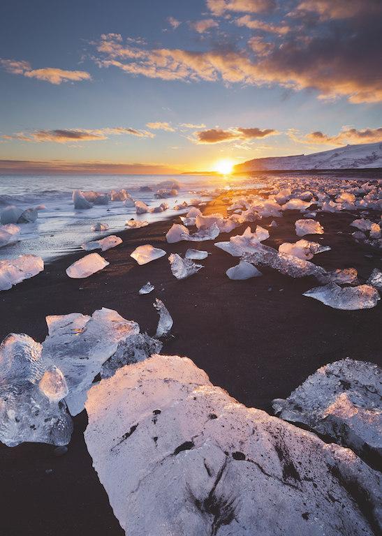 Zwei Belichtung: Eisblöcke auf schwarzem Sand in Island: Kontrastreicher geht es kaum! Eine Belichtung auf die Sonne und eine zweite auf das Eis lösten das Problem. In Photoshop wurden die beiden Bilder manuell mittels Ebenen kombiniert (Canon 5D Mk II, 24 mm, ISO 100, Blende 8, 1/8 s + 1/2s, Polfilter). Fotograf: Rainer Mirau