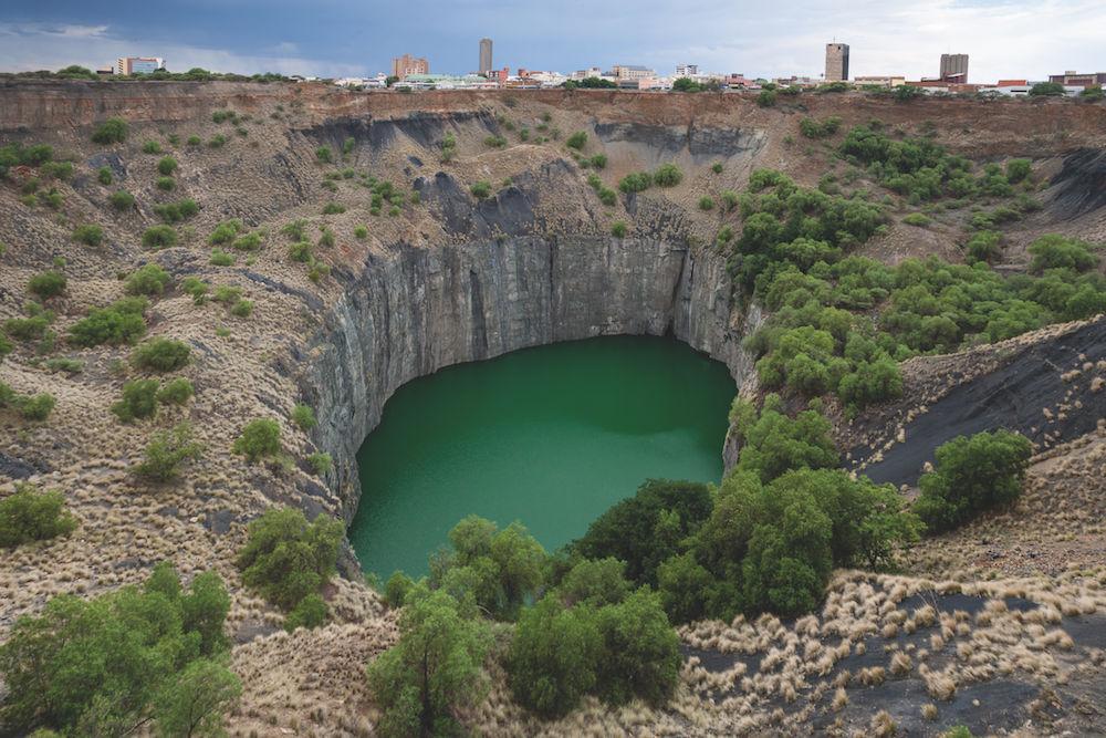 """Ein See und seine Geschichte: """"Das Große Loch"""" bei Kimberley in Südafrika, gefüllt mit Grundwasser, ist durch Diamantenabbau entstanden. Erst mit der Stadtsilhouette im Hintergrund entfaltet das Bild seine Wirkung. Foto: Siegfried Layda"""