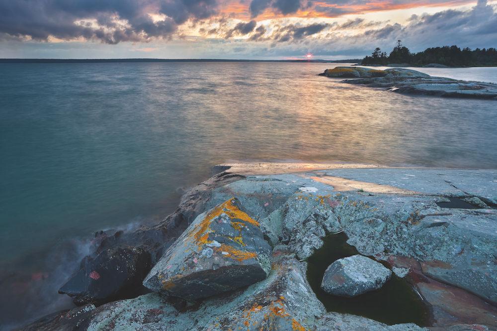 Dominanter Vordergrund: Der Lake Huron (Ontario, Kanada) ist fast 60.000 Quadratkilo meter groß. Die Felsen im Vordergrund mit den orange leuchtenden Flechten setzen einen starken Akzent. Foto: Rainer Mirau
