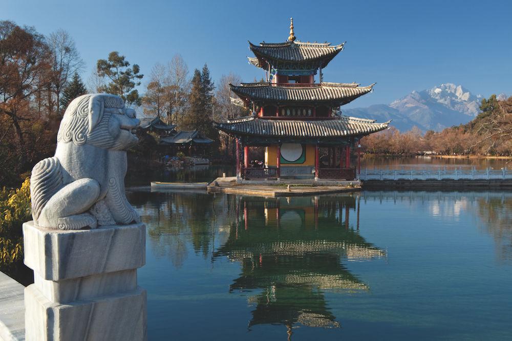 """Bildaufbau und Blickführung: """"Black Dragon Pool"""" in der chinesischen Provinz Yunnan im Ort Lijiang: Der Steinlöwe links vorne lenkt den Blick zur Pagode im mittleren Bildteil und weiter auf die Berge im Hintergrund. (Mitte) Foto: Siegfried Layda"""