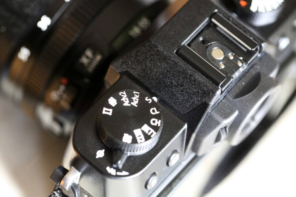 Auf der linken Seite findet sich ein Programmwahlrad (wie Du es von anderen Kameras kennt), allerdings ist die Belegung anders. Motivprogramme wirst Du keine finden, aber dafür Schnellzugriff auf z.B. Panoramafunktion und Bracketing