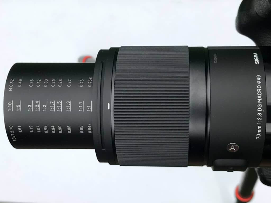Die Skala des SIGMA 70mm F2,8 DG MACRO | Art zeigt nicht nur die Distanz in Meter und Fuß an, sondern auch den jeweils korrespondierenden Abbildungsmaßstab.