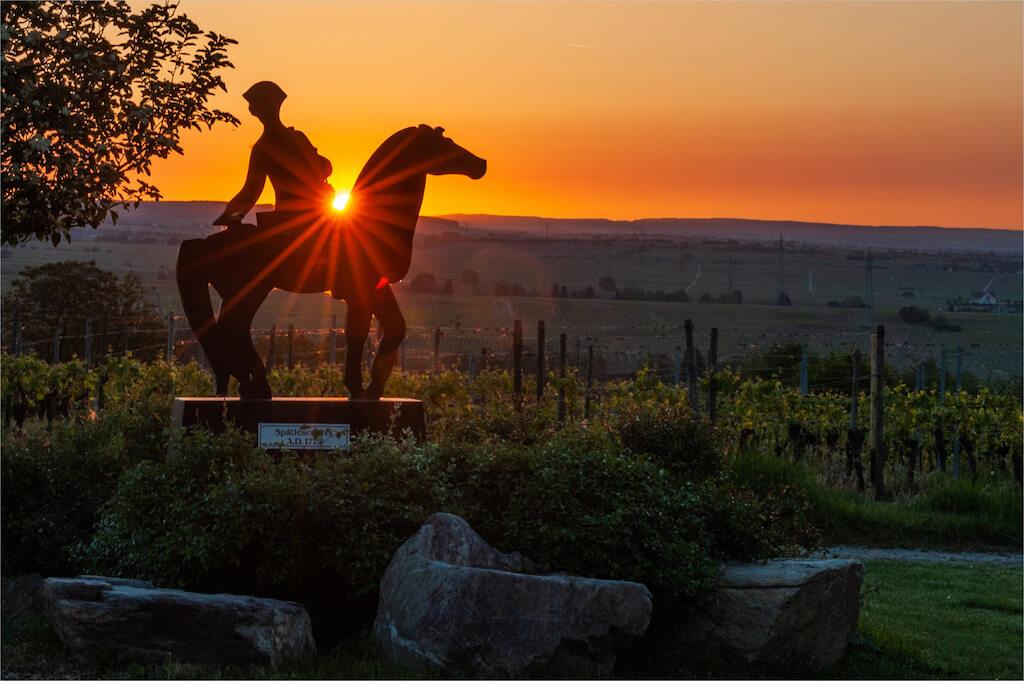 Das Denkmal des Spätlesereiter im Sonnenaufgang
